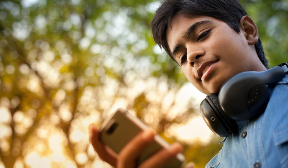 Happy teenager boy using mobile phone and headphones